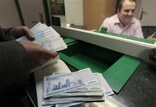 Мужчина пересчитывает белорусские рубли в обменном пункте банка в Минске, 15 сентября 2011 года. Национальный банк Белоруссии повысит с 11 ноября ставку рефинансирования до 40 процентов годовых с 35 процентов, сообщил Нацбанк. REUTERS/Vasily Fedosenko