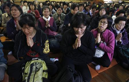 Mothers and grandmothers pray for their family members' success in the college entrance examinations, at a Buddhist temple in Seoul November 9, 2011.  REUTERS/Jo Yong-Hak