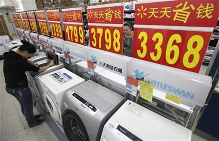Customers inspect washing machines at a supermarket in Wuhan, Hubei province November 8, 2011.  REUTERS/Stringer