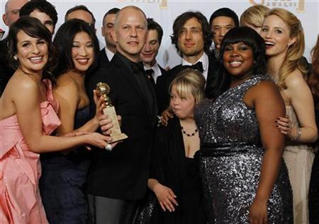 Ryan Murphy (3rd L), creator of the TV series 'Glee', and cast members including Lea Michele (L) and others pose with the award for best television comedy series at the 68th annual Golden Globe Awards in Beverly Hills, California, January 16, 2011.  REUTERS/Lucy Nicholson