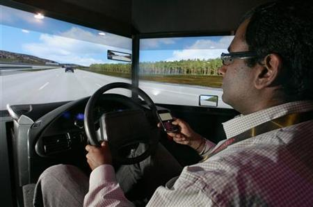 Kumar Chinnaswamy texts on his mobile phone while driving in a simulator at the LG booth during the 2010 International Consumer Electronics Show (CES) in Las Vegas, Nevada, January 7, 2010. REUTERS/Steve Marcus