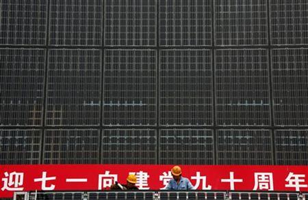 Workers stand atop scaffolding as they work on a building covered in solar panels located near the factory of the Yingli Green Energy Holding Company, also known as Yingli Solar, located in the city of Baoding, Hebei Province June 20, 2011. REUTERS/David Gray