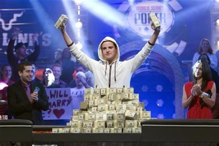 Pius Heinz of Germany holds up stacks of cash after beating Martin Staszko of the Czech Republic to win the championship bracelet and $8.7 million in prize money during the World Series of Poker main event at the Rio hotel-casino in Las Vegas, Nevada, November 9, 2011. REUTERS/Las Vegas Sun/Steve Marcus