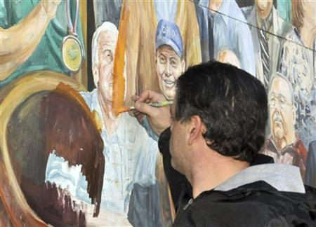 State College artist Michael Pilato paints over the portion of his mural that shows former Penn State assistant football coach Jerry Sandusky in downtown State College, Pennsylvania, November 9, 2011. REUTERS/Pat Little
