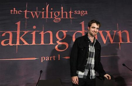 Cast member Robert Pattinson smiles while promoting ''Breaking Dawn'' from the Twilight Saga at the start of a news conference in Brussels October 26, 2011. REUTERS/Yves Herman