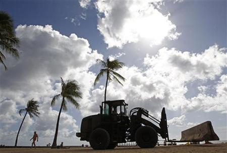 A U.S. Air Force forklift installs concrete barriers along Waikiki Beach before the annual APEC Summit in Honolulu, Hawaii November 9, 2011. REUTERS/Jim Young