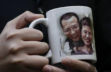 A protester holds a mug featuring an image of jailed Chinese dissident Liu Xiaobo and his wife Liu Xia outside Hong Kong's Legislative Council December 8, 2010, before several lawmakers leave for Oslo to attend the Nobel Prize presentation ceremony. REUTERS/Bobby Yip/Files