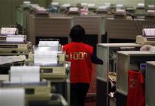 Трейдер проходит по торговому залу биржи в Гонконге, 14 марта 2011 года. Ключевые индексы фондовых рынков Японии и Кореи обвалились по итогам торгов четверга, после того как скачок доходности итальянских облигаций показал, что худший этап долгового кризиса Европы, возможно, еще впереди. REUTERS/Bobby Yip