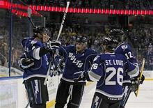 """Хоккеисты """"Тампы Бэй"""" радуются шайбе, заброшенной в ворота """"Виннипег Джетс"""", 29 октября 2011 года. Точный бросок форварда """"Тампа Бэй"""" Бретта Коннолли в дополнительное время принес его команде пятую подряд домашнюю победу в регулярном чемпионате НХЛ. REUTERS/Mike Carlson"""
