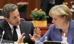 """Президент Франции Николя Саркози (слева) и канцлер Германии Ангела Меркель общаются на саммите в Брюсселе, 23 июня 2011 года. Германия и Франция обсуждали план радикальной """"реконструкции"""" Европейского союза, который может включать создание более сильно интегрированной зоны обращения единой валюты с меньшим количеством стран-членов, сообщили Рейтер источники в ЕС в среду. REUTERS/Thierry Roge"""