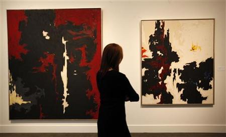 A woman looks at '1949-A-No.1' (L) and '1947-Y-No.2' by Clyfford Still on display at Sotheby's during a preview of their Impressionist and Modern Art sale in New York, October 28, 2011. REUTERS/Brendan McDermid