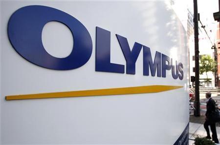 A man walks past a sign of Olympus Corp outside the company's showroom in Tokyo November 4, 2011.  REUTERS/Yuriko Nakao
