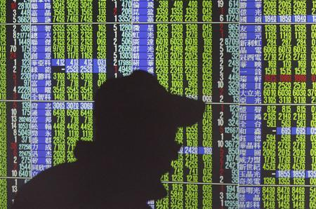 A man's shadow is cast on monitors displaying stock market prices inside a brokerage in Taipei November 10, 2011. REUTERS/Pichi Chuang