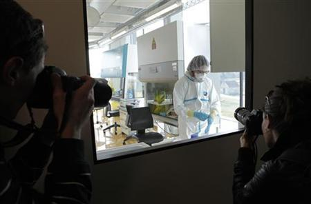 Photographers take a picture of a lab assistant preparing an experiment during an inauguration visit of a new P3 level research laboratory against tuberculosis at the School of Life Sciences of the Swiss Federal Institute of Technology (EPFL) in Lausanne in Ecublens near Lausanne  March 17, 2010. REUTERS/Denis Balibouse