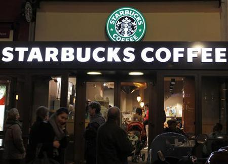 Customers are seen at a Starbucks coffee store which displays their old logo in Paris March 8, 2011.  REUTERS/Regis Duvignau