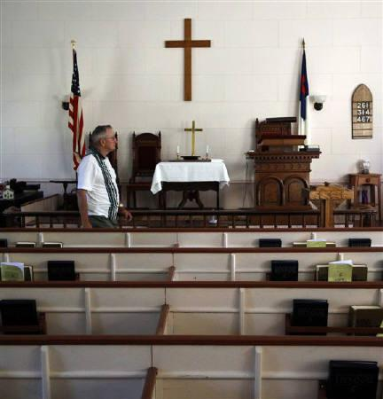 Howard Grace walks through the West Unity Community United Methodist Church before joining the weekly Bible study group in Unity, New Hampshire July 5, 2011. REUTERS/Brian Snyder