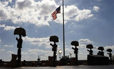 A memorial of rifles, boots and helmets, and a U.S. flag at half staff is seen at Fort Hood, Texas, November 10, 2009. REUTERS/Kevin Lamarque