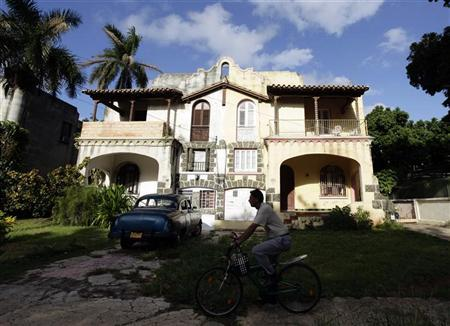 A man cycles beside a house in Havana's upmarket Miramar district, November 3, 2011.  REUTERS/Desmond Boylan