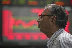 <p>A man monitors an electronic board displaying stock prices at the Karachi Stock Exchange November 10, 2011. REUTERS/Akhtar Soomro</p>