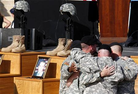 U.S. Army soldiers hug in front of fallen soldier memorials for the shooting victims during the III Corps and Fort Hood Memorial Ceremony at Fort Hood, Texas, November 10, 2009. REUTERS/Jessica Rinaldi