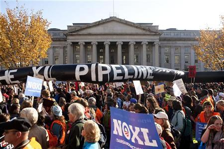 Demonstrators carry a giant mock pipeline while calling for the cancellation of the Keystone XL pipeline during a rally in Washington November 6, 2011.   Protesters are unhappy about TransCanada Corp's  plan to build the massive pipeline to transport crude from Alberta, Canada, to Texas.   REUTERS/Joshua Roberts
