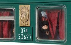 Трудовые мигранты выглядывают из окна вагона поезда, отправляющегося из Москвы в Таджикистан 7 октября 2011. Россия под аплодисменты националистов выслала свыше сотни трудовых мигрантов из Таджикистана после сурового приговора таджикского суда российскому пилоту. REUTERS/Denis Sinyakov