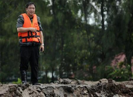 Kittirat Na Ranong, Thailand's deputy prime minister in charge of the economy, wears a life jacket as he inspects the work on a broken water barrier near Hi-Tech Industrial estate in Ayutthaya province October 13, 2011.  REUTERS/Damir Sagolj