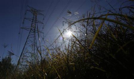 The sun shines above high tension power lines in an industrial area of west Sydney July 12, 2011. REUTERS/Daniel Munoz/Files