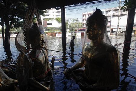 A man walks in front of a shop with protected golden statues of Buddha in a flooded neighborhood in Bangkok November 13, 2011. REUTERS/Kerek Wongsa