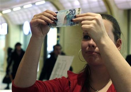 A vendor inspects a 20 Euro bank note in a shopping centre in Tallinn January 1, 2011.  REUTERS/Ints Kalnins