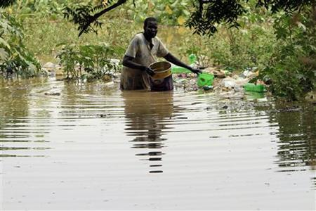A woman who lives near the bank of the River Nile collects her belongings after the river flooded in Khartoum August 21, 2010. REUTERS/Mohamed Nureldin Abdallah
