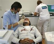 Пациент в стоматологическом кабинете в Крефельде, 28 сентября 2006 г. Регулярные посещения стоматолога могут дать больше, чем просто ослепительную улыбку. Согласно исследованиям тайваньских ученых, у людей, регулярно проводящих профессиональную чистку зубов, риск сердечного приступа меньше на 24 процента, а риск инсульта на 13 процентов ниже, чем у тех, кто никогда не проводил стоматологическую чистку зубов. REUTERS/Ina Fassbender