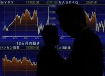 Люди проходят мимо электронного табло фондовой биржи Токио, 1 ноября 2011 г. Фондовые рынки Азии выросли по итогам торгов в понедельник в надежде на то, что технократические власти в Италии и Греции примут решительные меры для выхода из кризиса.REUTERS/Yuriko Nakao