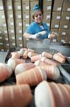"""Работница цеха по производству мороженого на молочном комбинате """"Ставропольский"""" в Ставрополе 7 июля 2011 года. Темпы роста валового внутреннего продукта (ВВП) РФ, по предварительным данным Росстата, ускорились в третьем квартале 2011 года до 4,8 процента с 3,4 процента во втором квартале. REUTERS/Eduard Korniyenko"""