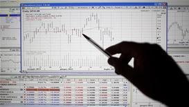 Мужчина изучает динамику фондового индекса. Фотография сделана в Риме 19 июля 2011 года. Италия привлекла в понедельник 3 миллиарда евро, разместив государственные облигации со сроком обращения 5 лет под доходность 6,29 процента. REUTERS/Max Rossi