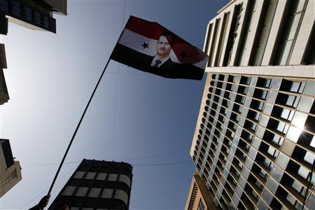 A Syrian living in Lebanon waves a flag of President Bashar al-Assad during a pro-Syrian government protest, in front of the Syrian embassy in Beirut November 13, 2011. REUTERS/Jamal Saidi