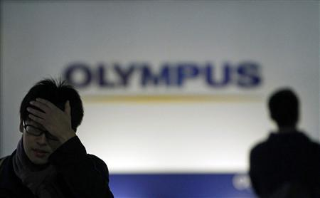 Men walk past a sign of Olympus Corp outside the company's showroom in Tokyo November 10, 2011. Tokyo's stock exchange warned scandal-hit Olympus Corp on Thursday it will be delisted after 62 years as a publicly traded company if it fails to report earnings by December 14, deepening concerns about the Japanese camera-maker's future.   REUTERS/Toru Hanai