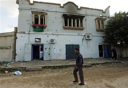 A man walks past a house that was damaged and looted by armed men, according to residents, during the three days of clashes between rival communities in Imaya west of Tripoli November 14, 2011.    REUTERS/Ismail Zitouny
