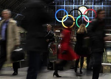 Commuters walk past the Olympic Rings, the symbol of the Olympic Games, at St Pancras international station in London March 3, 2011.   REUTERS/Eddie Keogh