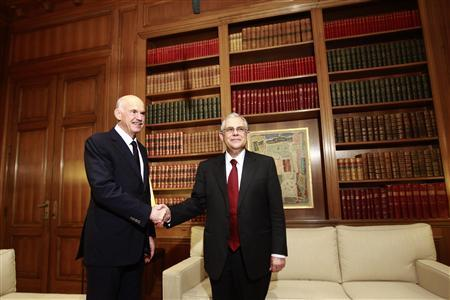 Newly appointed Greek Prime Minister Lucas Papademos shakes hands with outgoing Prime Minister George Papandreou at the Maximos mansion in Athens, November 11, 2011. REUTERS/John Kolesidis
