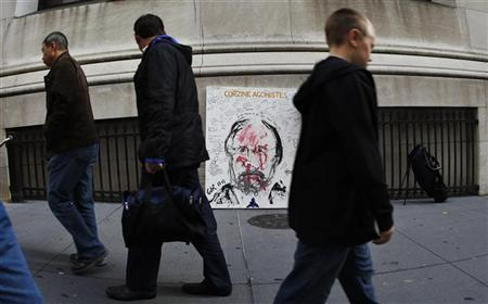 People pass Artist Geoffrey Raymond's latest painting ''Corzine Agonistes'' on Broad Street across from the New York Stock Exchange in New York, NOvember 10, 2011.  REUTERS/Mike Segar
