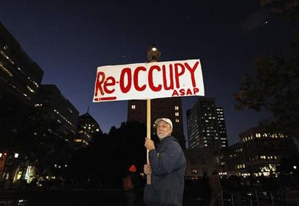 A demonstrator holds up his sign at City Hall plaza in Oakland, California November 14, 2011.     REUTERS/Kim White