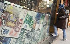 Женщина стоит около пункта обмена валют в Тегеране, 24 октября 2011 года. Российская железнодорожная монополия РЖД рассматривает азиатские площадки в качестве одного из вариантов для размещения еврооблигаций в 2012 году, объем и валюта которых будут определены по итогам текущего года, сообщил во вторник глава компании Владимир Якунин. REUTERS/Raheb Homavandi