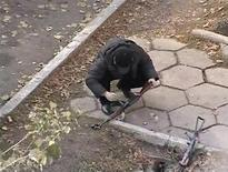 На фрагменте видеозаписи полицейский следователь, изучающий автомат Калашникова, брошенный на месте атаки боевика-исламиста в Таразе 12 ноября 2011. Бессменный президент Казахстана Нурсултан Назарбаев, ставивший себе в заслугу стабильность, сказал, что она проходит испытание на прочность в столкновении с терроризмом, жертвами которого он назвал семерых погибших в минувшую субботу на юге. REUTERS/Reuters TV