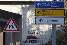 """Дорожные знаки на фоне антинацистского граффити. Фотография сделана в Цвиккау 12 ноября 2011 года. В Германии возник """"новый тип праворадикального терроризма"""", заявил министр внутренних дел в воскресенье после появления сведений о фильме, предположительно снятом группой неонацистов, заявивших об убийстве ими девяти иммигрантов в 2000-2006 годах.  REUTERS/Tobias Schwarz"""