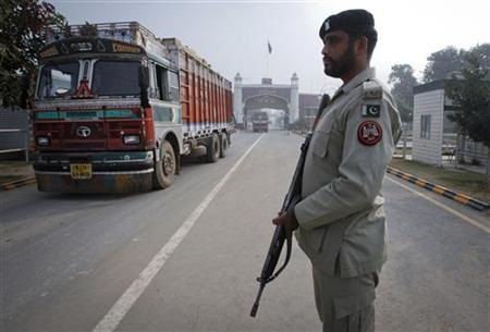A paramilitary soldier stands guard as a truck crosses into Pakistan from India, at the Wagah border, Pakistan, November 4, 2011. REUTERS/Mohsin Raza