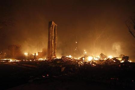 The chimney of a house remains standing as the rest of the building burns to the ground near Bastrop, Texas, September 5, 2011.   REUTERS/Mike Stone