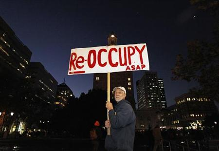 A demonstrator holds up his sign at City Hall plaza in Oakland, California November 14, 2011.  Police moved in early on Monday and cleared out anti-Wall Street protesters from Oakland's City Hall plaza, arresting 32 people but avoiding the sort of clashes that marked a previous attempt to shut down the Occupy Oakland camp.  REUTERS/Kim White
