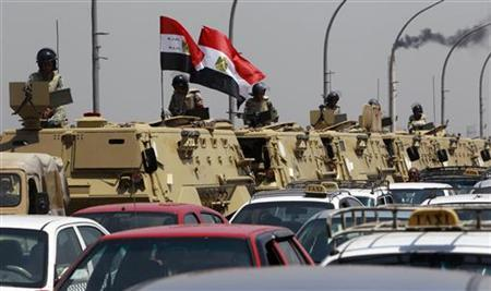 Egyptian army vehicles are parked near the Israeli embassy as protesters shout slogans against Israel during a protest in front of the Israeli embassy in Cairo August 21, 2011. REUTERS/Amr Abdallah Dalsh