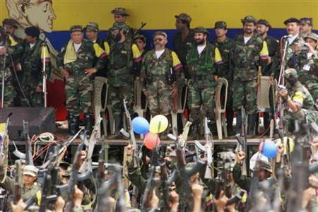 Colombian leftist commanders (L to R) Manuel Marulanda, known as ''sureshot'', Alfonso Cano, peace negociator Raul Reyes, Timochenko, Ivan Marquez and Jorge Briceno, all members of the general secretariat of the Armed Revolutionary Forces of Colombia (FARC), watch a parade of armed fighters in the camp at Villa Colombia near San Vicente del Caguan, April 29. REUTERS